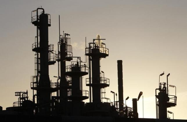 Towers and smokestacks are silhouetted at an oil refinery in Melbourne